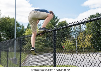 Teenage Boy jumping over a school yard fence, Canada.