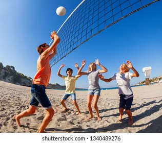 Teenage boy jumping to spike volleyball over net