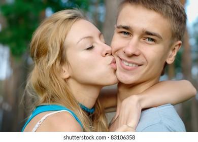 Teenage boy kissed by his girlfriend