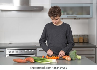 Teenage Boy in the kitchen cutting vegetables