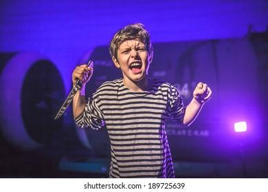 teenage boy with knife brandishing threat of night attacks prisoner blue background
