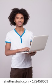 Teenage boy with laptop. Cheerful African teenager working on laptop and smiling at camera while standing isolated on grey background