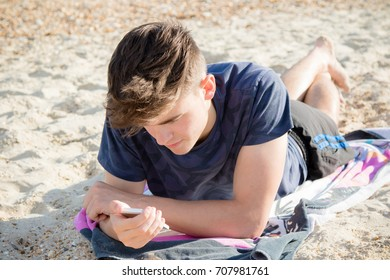 Teenage boy laying on a beach using a mobile phone