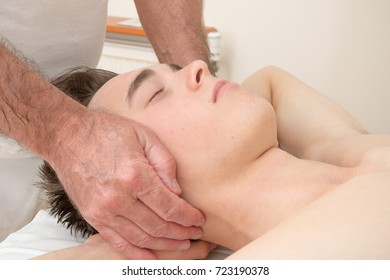 Teenage boy laying on a massage table, having a head massage