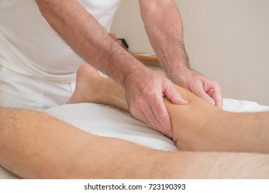 Teenage boy laying on a massage table, having a leg massage