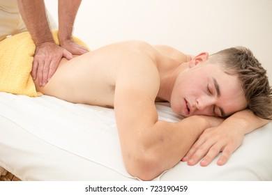 Teenage boy laying on a massage table, having a back massage