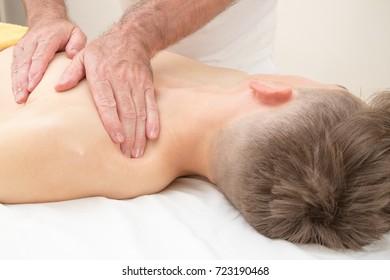 Teenage boy laying on a massage table, having a massage
