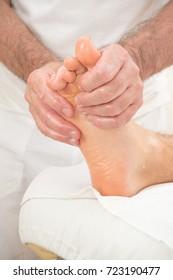 Teenage boy laying on a massage table, having a foot massage