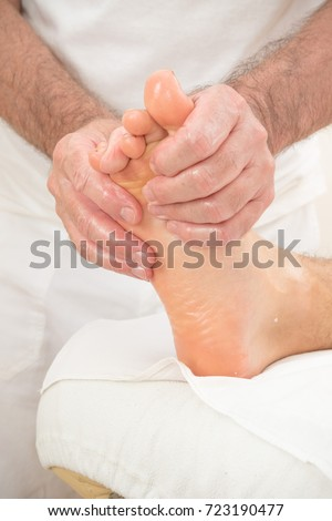 Teenage boy laying on a massage table, having a foot massage