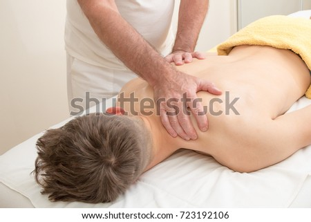 Teenage boy laying on a massage table, having a back massage