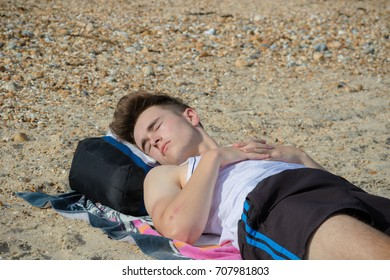 Teenage boy laying on a stoney beach