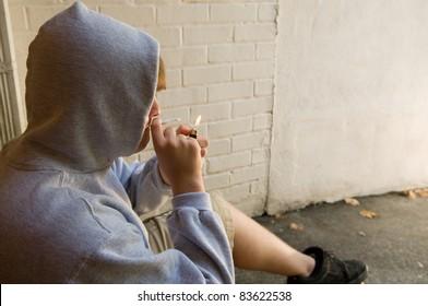 teenage boy lighting marijuana cigarette in grungy urban setting