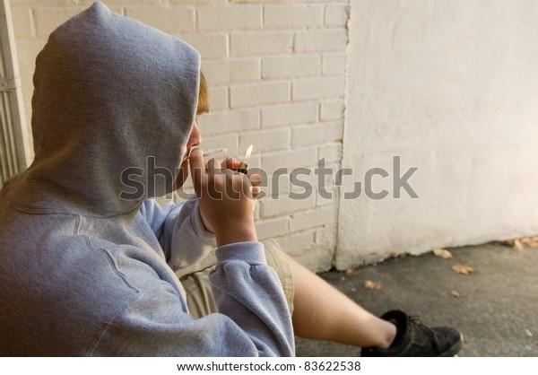 teenage boy lighting marijuana cigarette in grungy urban setting