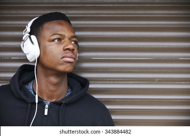 Teenage Boy Listening To Music In Urban Setting