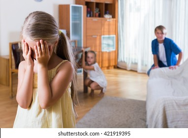 Teenage boy with little sisters playing hide-and-go-seek in flat