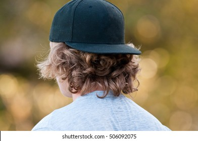 Teenage boy with long hair looking away in a black baseball hat.