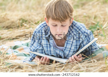 Teenage boy lying with a book outdoor
