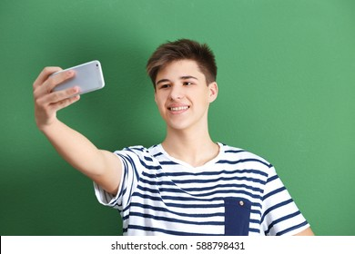 Teenage boy making selfie with mobile phone on color background