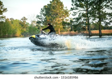 Teenage boy man driving a personal watercraft outside on a lake pond at sunset