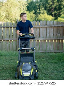 Teenage boy mowing the lawn for summer chores.