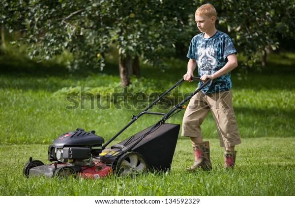Teenage Boy Mowing Lawn Using Lawn Mower