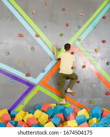 Teenage boy on climbing wall in trampoline center. Adventure and extreme for teenager concept