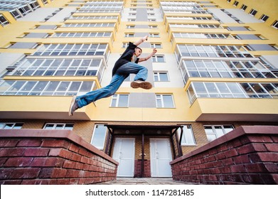 Teenage boy on a street in a big city next to a high-rise building alone. concept of a teenager parkour life. parkour jump on a high-rise building background from the side close up view
