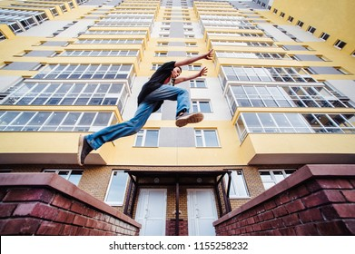 Teenage boy on a street in a big city next to a high-rise building alone. concept of a teenager parkour life. parkour jump on a high-rise building background from the side close