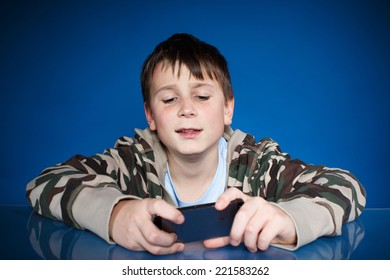 teenage boy with phone in hand on blue background