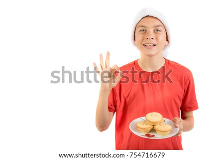Teenage boy with a plate of mince pies giving positive gestures