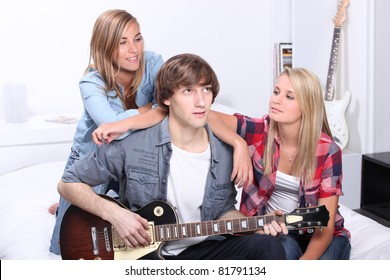 teenage boy playing electric guitar next to two girls