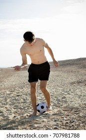 Teenage boy playing with a football on a beach