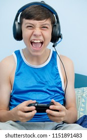 Teenage boy playing a video game while on his bed, yelling