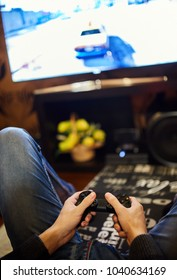 Teenage boy playing videogames, sitting on sofa
