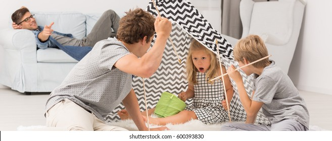Teenage boy playing with younger siblings in tipi tent