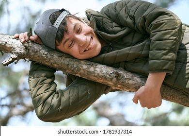 teenage boy poses on a tree, lying on a big branch and dreaming