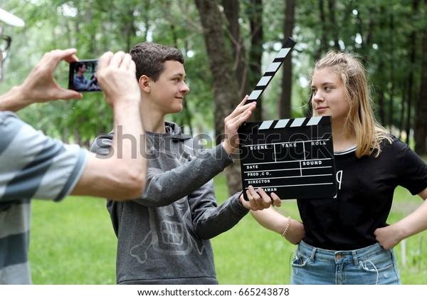 Teenagerjunge mit realistischem Klappkino-Board bereit, ein lustiges Video mit Studentenmädchen im Park aufzunehmen, ein Senior-Mann, der Smartphone hält, um ein Video, Bildung und Technologie zu machen, im Sommer im Freien
