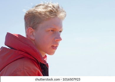 Teenage boy with red floatation suit against sky