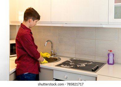 Teenage Boy in a red-colored shirt  wearing rubber protective yellow gloves cleaning the kitchen at his home. Home, housekeeping concept. The teenager helps around the house.
