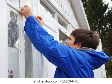 Teenage boy is repairing an old wood window. He is outside. He is wearing warm clothes and a blue windcheater. He has concentrated look.