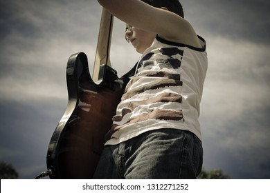 A teenage boy rocks out with his guitar on stage at an outdoor concert. Dressed in a flag embellished tank top, he plays the National Anthem during a Fourth of July event.
