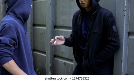 Teenage boy secretly buying cocaine from afro-american dealer, drug addiction