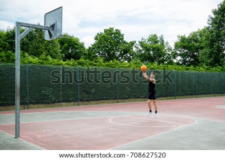 Teenage boy shooting a basketball on a court
