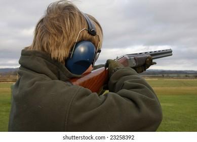 Teenage boy shooting at the clay pigeon