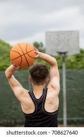 Teenage boy shooting a hoop on a basketball court
