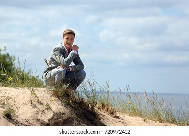 Teenage boy sits on sand dune - rest on beach - cloudy blue sky and sea background