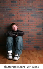 teenage boy sitting against a wall and depicting the concept of loneliness