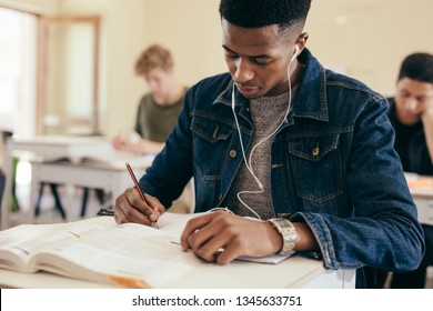 Teenage boy sitting in high school classroom writing in book. Male student with earphones on, making notes during lecture in college classroom.