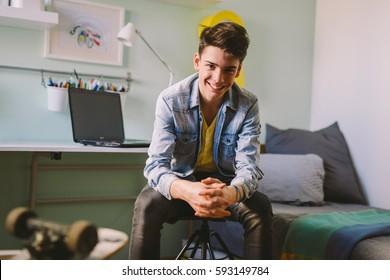 Teenage boy sitting  in his room