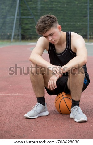 Teenage boy sitting on a basketball on a court looking sad